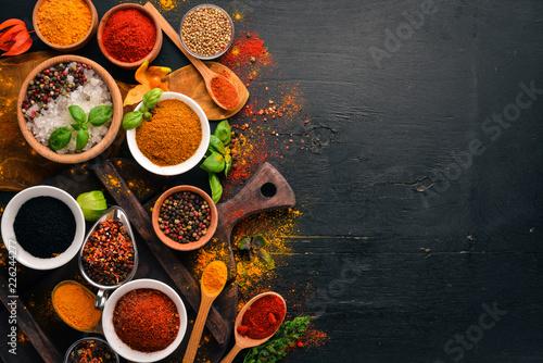 Leinwandbild Motiv Spices and herbs on a wooden board. Pepper, salt, paprika, basil, turmeric. On a black wooden chalkboard. Top view. Free copy space.
