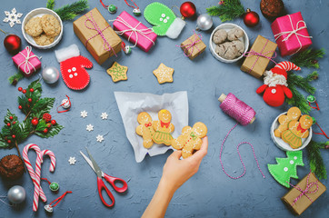 Christmas background with gifts, cookies, Christmas decoration and woman's hands holding cookies