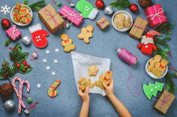 Christmas background with gifts, cookies, Christmas decoration and children's hands holding gingerbred cookies
