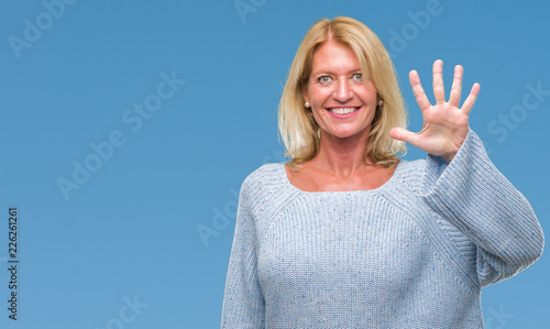 Foto Murales Middle age blonde woman wearing winter sweater over isolated background showing and pointing up with fingers number five while smiling confident and happy.