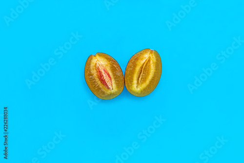 Halves of ripe blue plum with bone isolated on bright color background, minimalism style, copy space top view,   - 226288034