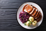Festive German full dinner Sauerbraten - beef stew with gravy served with potato dumplings and red cabbage close-up. horizontal top view