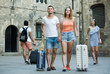 Joyful man and woman in shorts with luggage