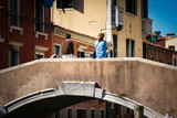 Travel to Italy.Travel to Italy. People enjoying a glass of wine on a bridge over the canal in Venice, Italy. . Europe travel vacation. Woman traveling to Venice.