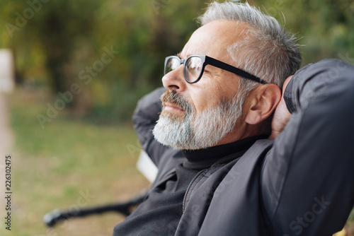 Foto Murales älterer mann sitzt entspannt im park