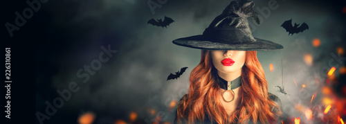 Leinwandbild Motiv Halloween. Sexy witch portrait. Beautiful young woman in witches hat with long curly red hair over spooky dark magic forest background