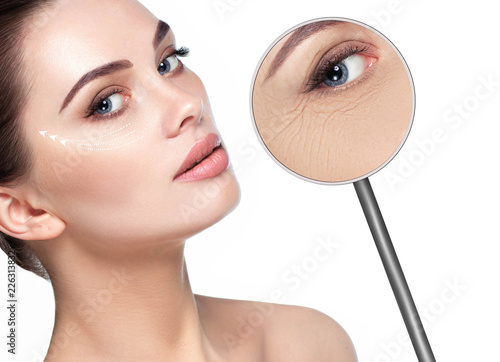 beautiful woman face with lifting arrows on skin and magnifying glass showing aging skin around eyes. Wrinkles around the eyes, the procedure for rejuvenating dry and aging facial skin, mesotherapy