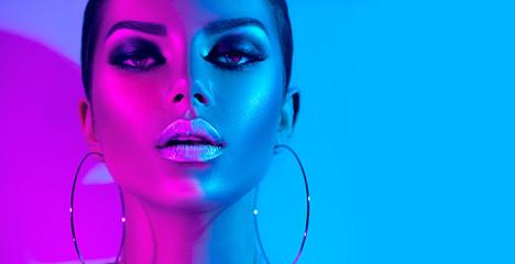 Fashion model brunette woman in colorful bright neon lights posing in studio. Beautiful sexy girl, trendy glowing makeup, metallic silver lips