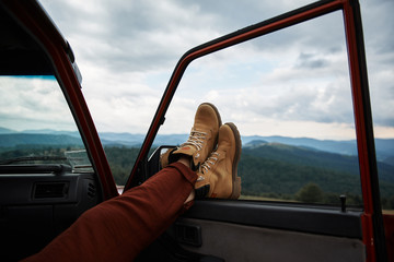 Close up of feet of a relaxed traveler holding them on the window while enjoying mountains view
