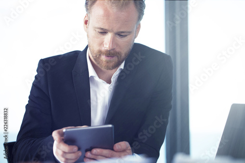 Leinwanddruck Bild Businessman works with a tablet during a meeting
