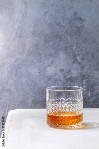 Glass of scotch whiskey standing on white marble table with grey wall at background. Alcohol drink.