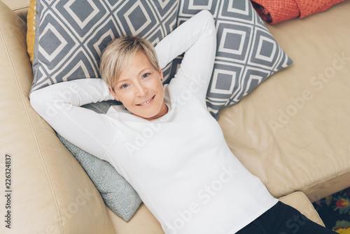 Leinwandbild Motiv frau liegt auf dem sofa auf kissen