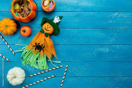 Leinwandbild Motiv Table top view aerial image of decoration Happy Halloween day background concept.Flat lay accessories essential object to party the pumpkin  & cute doll on blue wooden.Space for creative design.