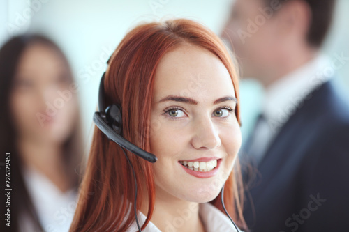 Foto Murales Portrait of a smiling creative businesswoman with earpiece in office