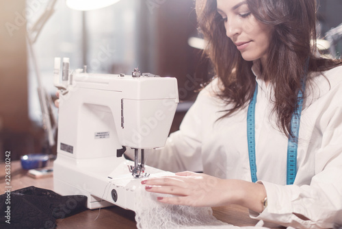 Close-up view of sewing machine and young female tailor working on it while sitting in a workshop