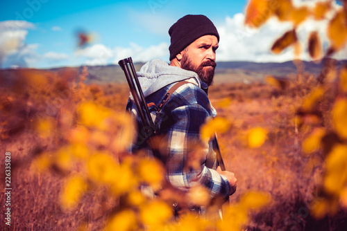 Autumn hunting season. Hunter with shotgun gun on hunt. Autunm hunting. Poacher with Rifle Spotting Some Deers. Close up Portrait of hamdsome Hunter.