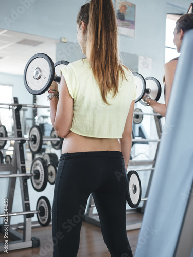 Poster attractive young female exercising in a gym