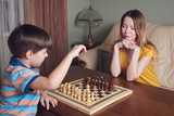 Mother and son are playing chess at home.