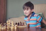 Smiling caucasian boy is playing chess at home.