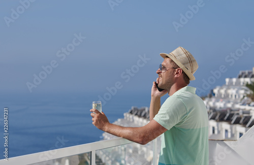 Happy man in sun hat with glass of sparkling wine talking on mobile phone  and looking 4f0fc692a8fb