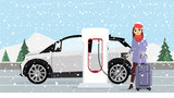 Woman charges an electric car at a charging station for electric vehicles. Winter time. Snow.