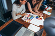 Two female architects working together using color swatches sitting at desk with laptop, graphic tablet in design studio