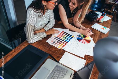 Dwa żeńskiego architekta pracuje wpólnie używać colour swatches siedzi przy biurkiem z laptopem, graficzna pastylka w projekta studiu