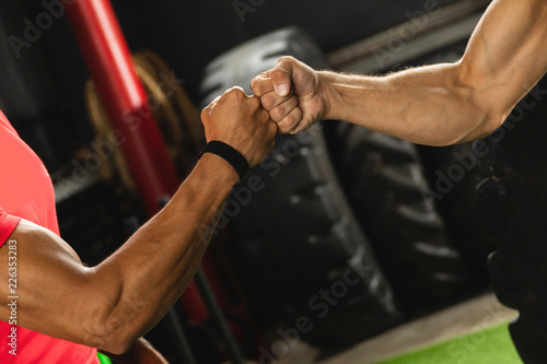 Poster Two muscular men are making fist bump gesture during workout in the gym