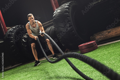 Poster Man is making battle rope exercises during his cross training workout