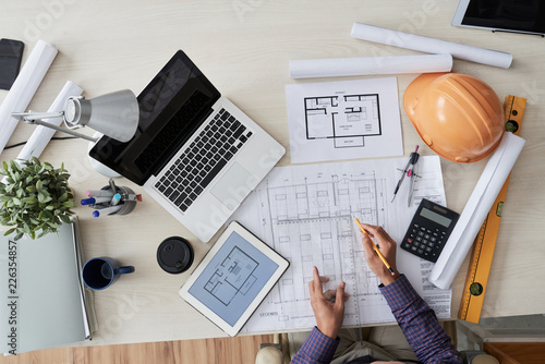 Foto Murales Construction engineer working with various blueprints on his table, view from above