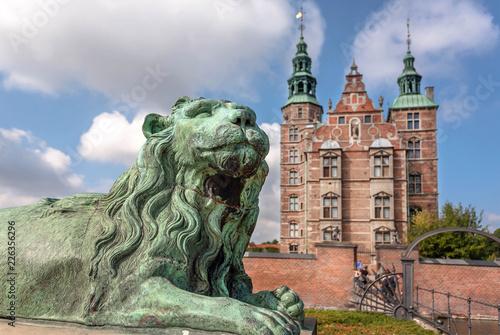 Tower spires over lion bronze sculpture guard at the entrance of Rosenborg Castle, built in 17th century. Historical landmarks of Copenhagen, Denmark