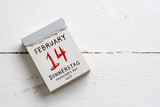 Tear-Off Calendar with Valentine's Day 2019 on top on wooden background