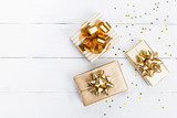 Heap of gift or present boxes and stars confetti on white wooden table top view. Flat lay composition for birthday, christmas or wedding.