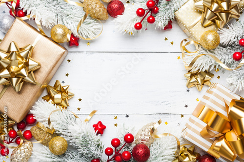 Golden gifts or presents boxes, snowy fir tree and christmas decorations on white wooden table top view. Flat lay. - 226362669