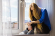 Leinwandbild Motiv Sad depressed teen girl sitting on window sill
