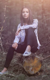 beautiful young woman sitting on a log - 226392494