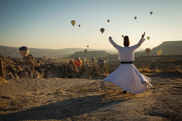 Dervish doing the retual in love valley of Cappadocia with balloons in background at sunrise.