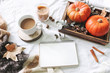 Autumn breakfast in bed composition. Blank calendar, notebook mockup. Cup of coffee, eucalyptus leaves and pumpkins on wooden tray. White linen background. Thanksgiving, Halloween holiday. Top view.