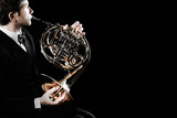 French horn player. Hornist playing brass orchestra music instrument - 226399632
