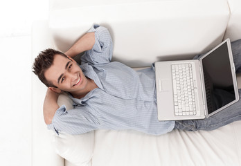 guy working on laptop lying on a sofa