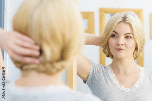 Happy woman doing her hairstyle