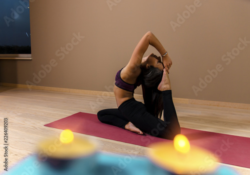 Fototapeta Attractive girl in yoga pose, candles in foreground / swan pose