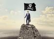 Leinwandbild Motiv Successful businessman on the top of a mountain holding pirate flag