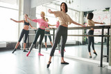 Full length portrait of three elegant young women practicing ballet moves standing by bar against mirror in dance studio, copy space - 226415653
