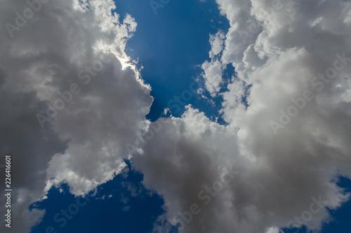 Blue sky, cumulus clouds, sunlight. - 226416601