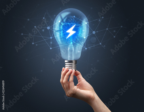 Foto Murales Hand holding light bulb on dark background. Networking idea concept