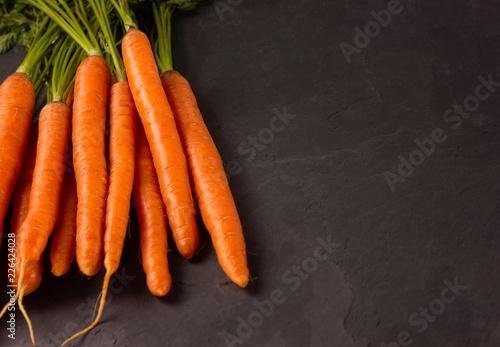 Leinwanddruck Bild Bunch of raw carrots on dark background.