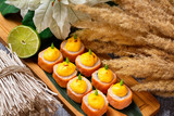 Fototapeta Maki - Set of hot philadelphia sushi rolls at decorated restaurant table background. © mayatnik