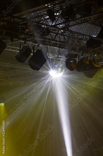 Stage lights. Soffits. Concert light. Silver mirror disco ball in the rays of the spotlights - 226445683