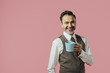 Leinwanddruck Bild - Smiling mature man holding coffee mug, isolated on pink studio background